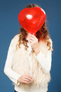 Young cute girl with heart shaped ballon over blue background Stock Photography