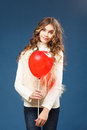 Young cute girl with heart shaped ballon over blue background Stock Photo