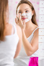 Young cute girl putting facial mask on her face reflection of Royalty Free Stock Images