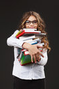 Young cute girl with stack of books holding in her hands over grey background Stock Photography