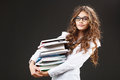 Young cute girl with stack of books holding in her hands over grey background Stock Photos