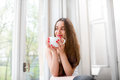 Young and cute lady drinking coffee on the windowsill and lookin looking out window Royalty Free Stock Photo