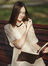 Young cute lady sitting on bench reading book Stock Photography