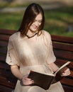 Young cute lady sitting on bench reading book Stock Image