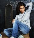 Young cute teenage girl in classroom at blackboard seating on ta