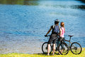 Young cyclist couple watching the lake standing and Royalty Free Stock Photos