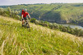 Young cyclist cycling in the green summer meadow against beautiful landscape. Royalty Free Stock Photo