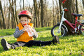 Young cyclist enjoying a drink of refreshing water from plastic bottle sitting on the green grass amongst the trees in rural Stock Images