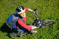 Young cyclist on green grass a mountain bike Stock Photos
