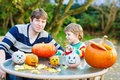 Young dad and his little son making jack o lantern for halloween in autumn garden outdoors family having fun together Stock Photos