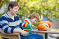 Young dad and his little son making jack o lantern for halloween in autumn garden outdoors family having fun together Stock Photography