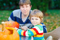 Young dad and his little son making jack o lantern for halloween in autumn garden outdoors family having fun together selective Stock Photo