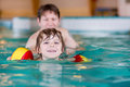 Young dad teaching his little son to swim indoors Royalty Free Stock Photo