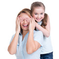 Young daughter closes hands eyes mom isolated happy family people concept Stock Photos