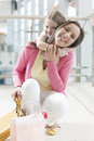 Young daughter hugs mother in shopping mall Stock Photography