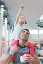 Young daughter points and sits on fathers shoulders Royalty Free Stock Photo