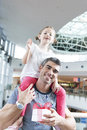 Young daughter sits on fathers shoulders Royalty Free Stock Photo