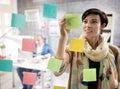 Young designer in studio makes sketch on memo stickers female design make Stock Photos