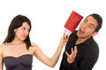 Young disappointed woman hits man with gift bag Royalty Free Stock Photo