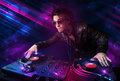 Young DJ playing on turntables with color light effects Royalty Free Stock Images