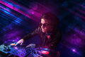 Young dj playing on turntables with color light effects attractive Royalty Free Stock Photography