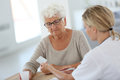Young doctor giving medication to elderly woman pills Royalty Free Stock Photos