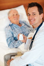 Young doctor giving pills to an elderly patient Royalty Free Stock Image