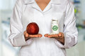 Young doctor holding apple and bottle of pills with vitamins and Royalty Free Stock Photo