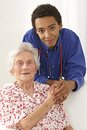 Young Doctor holding elderly lady's hands at home Royalty Free Stock Photo