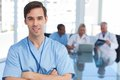 Young doctor holding a file with arms crossed standing in front of his team Royalty Free Stock Image