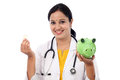 Young doctor woman holding a piggy bank Royalty Free Stock Photo