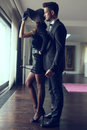 Young dominant rich man with whip embracing lover Royalty Free Stock Photo