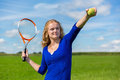 Young dutch woman holding tennis racket and ball outdoors Royalty Free Stock Photo