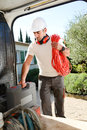 Young electrician artisan taking tools out of professional truck van Royalty Free Stock Photo