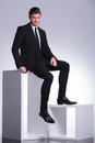 Young elegant business man sitting on a white table handsome holding foot smaller Stock Photos