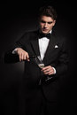 Young elegant man pouring wine in a glass while looking down Stock Photos