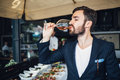 Young elegant man standing in the restaurant holding a glass of wine man s style stylen Stock Photos