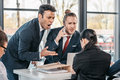 Young emotional businesspeople in formalwear arguing at meeting in office Royalty Free Stock Photo