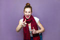 Young emotional girl with collected hair, freckles and red scarf looking excited on purple background, pointing. Royalty Free Stock Photo