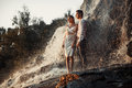 Young enamored couple stands on rock under spray of waterfall. Royalty Free Stock Photo