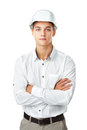 Young engineer wearing a white helmet portrait of standing with hands folded against isolated on background Royalty Free Stock Photography