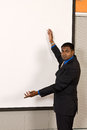 Young ethnic business man at an off white projector screen makes a gesture with his arms Royalty Free Stock Photos