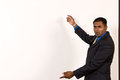 Young ethnic business man at an off white projector screen makes a gesture with his arms Stock Image