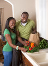 Young ethnic couple on kitchen sorting groceries Royalty Free Stock Photo