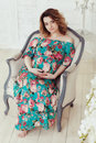 Young, extravagant, extraordinary pregnant girl, woman sitting on a chair in the flowerpot snake modern dress white Royalty Free Stock Photo
