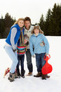 Young Family In Alpine Snow Scene With Sleds Stock Photography