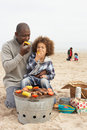 Young Family Enjoying Barbeque On Beach Stock Images