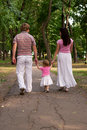 Young family father mother toddler daughter walking park rear view family dressed similar clothing Stock Photos