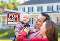 Young Family In Front of For Sale Sign and House Royalty Free Stock Photo