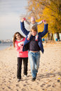 Young family having fun on beach at autumn portrait of Stock Photo